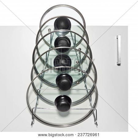 A Hanger With Glass Lids For Cooking Pots Hung On The Door Of A Kitchen Cupboard.