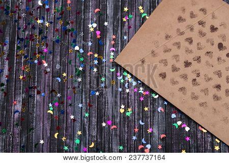 Envelope Of Kraft Paper. Love Letter Envelope. Wooden Background. Social Network. Sequins Scattered