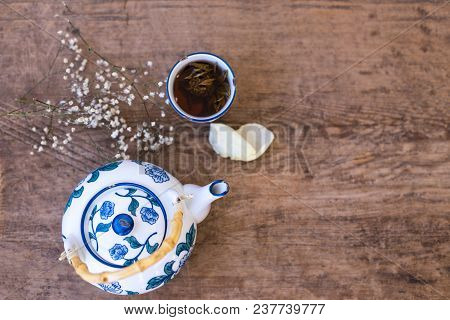 Top View Shot Of A White And Blue Tea Pot And A Cup Of Herbal Tea On Rustic Wooden Tabletop. Copy Sp