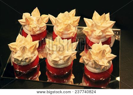 Six Original Cakes On The Mirror On A Dark Background