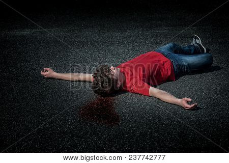 Crime Scene - Dead Teen Boy Body In Blood On Asphalt - Staged Photo. Body Of A Young Childlying On T