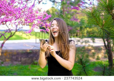 Laughing Girl Using Smartphone In Garden With Blooming Trees Background. Concept Of Wireless Interne