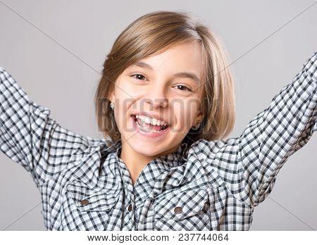 Beautiful Caucasian Teen Girl On Gray Background. Schoolgirl Looking At Camera. Funny Cute Teenager