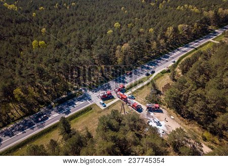 Aerial View Of A Car Accident, Police, Firefighters And An Asphalt Road In A Summer Forest