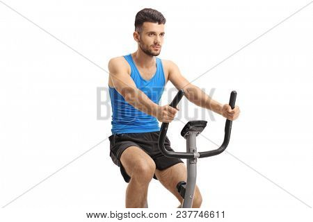Young man exercising on a stationary bike isolated on white background