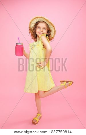 Stylish Little Girl In Yellow Dress And Straw Hat Posing With Glass Of Pink Lemonade Holding Hand On