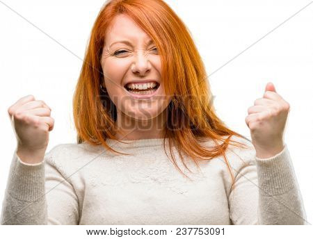 Beautiful young redhead woman happy and excited expressing winning gesture. Successful and celebrating victory, triumphant isolated over white background