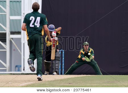PUCHONG, MALAYSIA - SEPT 24: Tom Kimber, Guernsey eyes the ball hit by Faris Lee, Malaysia in this Pepsi ICC World Cricket League Div 6 finals at the Kinrara Oval on Sept 24, 2011 in Puchong, Malaysia