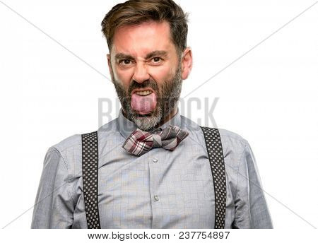 Middle age man, with beard and bow tie feeling disgusted with tongue out isolated over white background