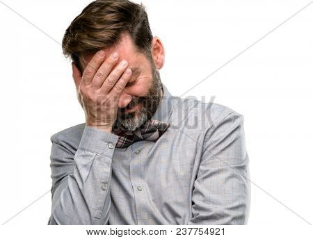 Middle age man, with beard and bow tie stressful keeping hands on head, tired and frustrated isolated over white background