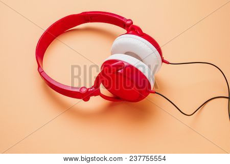 Photo of red with white headphones on peach background