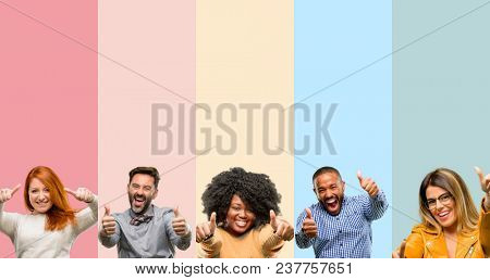 Cool group of people, woman and man stand happy and positive with thumbs up approving with a big smile expressing okay gesture