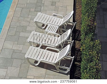Three Plastic Sun Chairs By The Pool