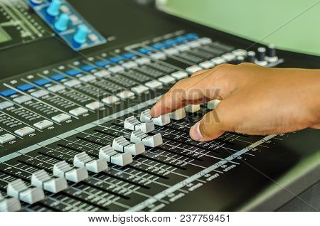 Sound Technician Hands Working On Audio Mixer Faders And Knobs. Shallow Depth Of Field. Music Produc