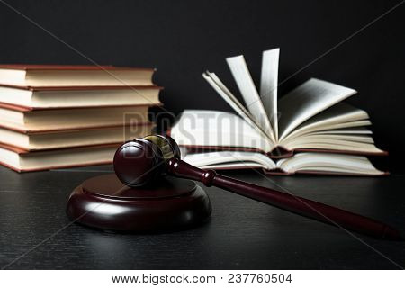 Judge Gavel Beside Pile Of Books On Black Wooden Background