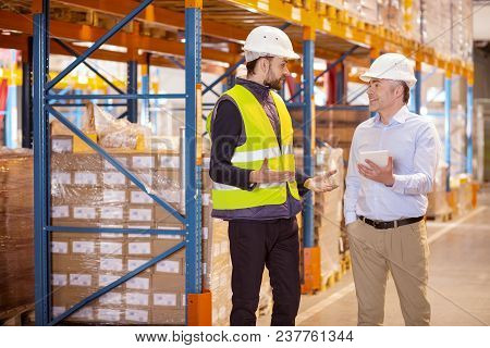 At Work. Nice Young Man Talking To The Logistics Manager While Working In The Warehouse