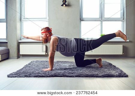 A Funny Fat Bearded Man In Sports Clothes Does Yoga In The Room. A Fat Man Is Engaged In Sports.