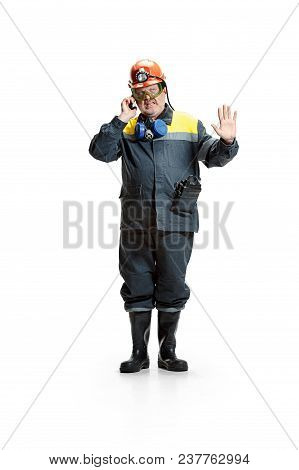 Studio Shot Of Disgusted Senior Bearded Male Miner In Professional Helmet With Smartphone Standing A
