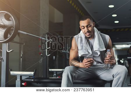 Social Networks. Young African-american Man Messaging On Smartphone At Gym, Having Rest After Workou