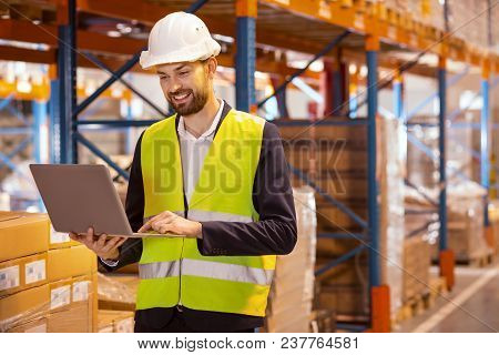 Large Scale Distribution. Professional Delivery Manager Using Laptop For His Work While Dealing With