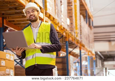 Professional Occupation. Smart Logistics Manager Smiling While Working In The Big Storehouse
