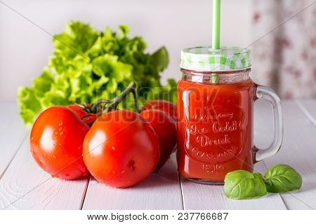 Tomato Juice In A Transparent Glass On A Wooden Table.