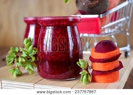 Red Vegetable Smoothie Made Of Carrot And Beetroot In Glass Jars On Wooden Background