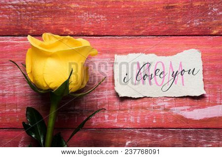 a yellow rose and a piece of paper with the text I love you mom written in it, on a red rustic wooden surface