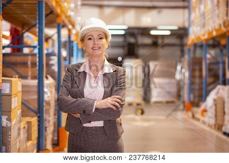 Professional Manager. Confident Pleasant Woman Looking At You While Working In The Storehouse.