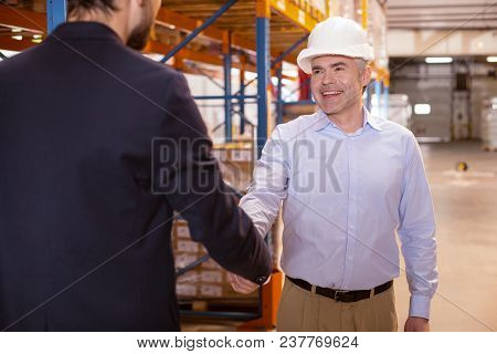 Work Meeting. Joyful Positive Man Smiling While Greeting His Boss In The Warehouse