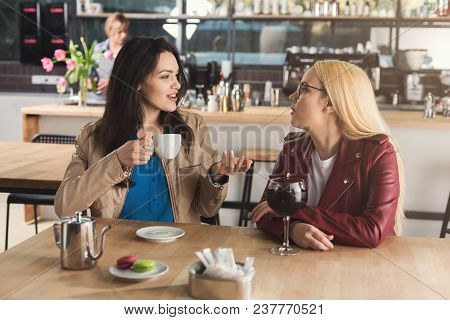 Happy Young Girl Friends Drinking Coffee, Talking And Smiling While Sitting At Modern Bar Interior,