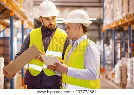 Quality Control. Nice Serious Smart Man Holding A Tablet While Checking The Package In The Warehouse