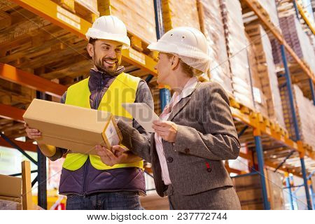Delivery Managing. Nice Pleasant Woman Talking To The Delivery Man While Controlling The Delivery Se