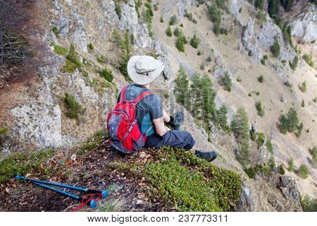 male hiker sitting on top of a mountain admiring the view