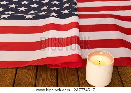American Flag And Memorial Candle On Veterans Day . On Wooden Background  .