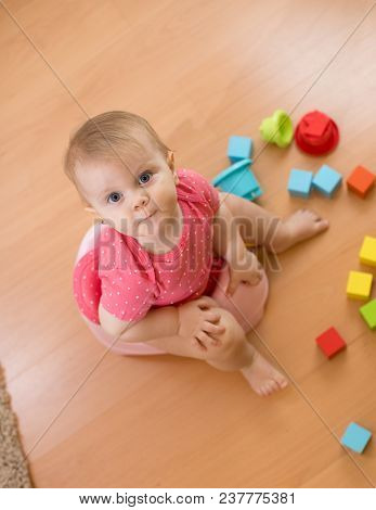 Baby Girl Sitting On Chamber Pot And Playing With Toys. Top View.