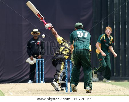 PUCHONG, MALAYSIA - SEPT 24: Guernsey's Tom Kimber (57) watches Malaysia's Ahmad Faiz bat at the Pepsi ICC World Cricket League Div 6 finals at the Kinrara Oval on Sept 24, 2011 in Puchong, Malaysia.