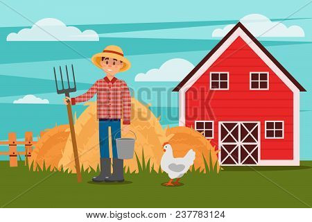 Young Male Farmer With Pitchfork And Bucket. Chicken Walking On Green Meadow. Heaps Of Hay, Wooden F