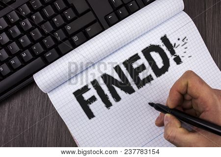 Conceptual hand writing showing Fined Motivational Call. Business photo text No penalty charge for late credit card bill payment written by Marker in Hand Notebook wooden background Keyboard poster