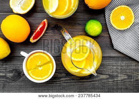 Hot Fragrant Tea With Fruits. Teacup And Teapot Near Citruses On Dark Wooden Background Top View.