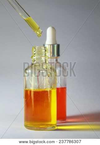 A Drop Of Bright Useful Cosmetic Oil Drops From A Transparent Pipette Into Two Glass Transparent Bot