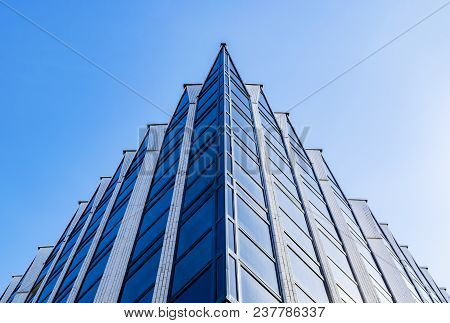 Detail Of Office Building Exterior. Business Buildings Skyline Looking Up With Blue Sky. Modern Arch