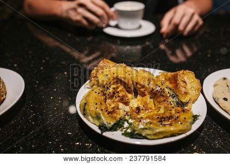 A Person At The Restaurant Who Is Preparing To Eat Traditional Turkish Dish Called Burek. Compositio