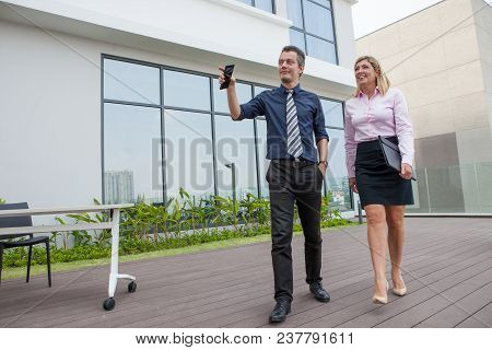 Content Middle-aged Business Man And Woman Walking And Chatting Outdoors With Building In Background