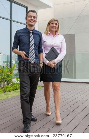 Happy Attractive Middle-aged Male And Female Business People Walking Outdoors With Building In Backg