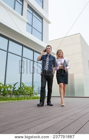 Smiling Attractive Male And Female Business People Relaxing Outdoors On Modern Office Rooftop With F