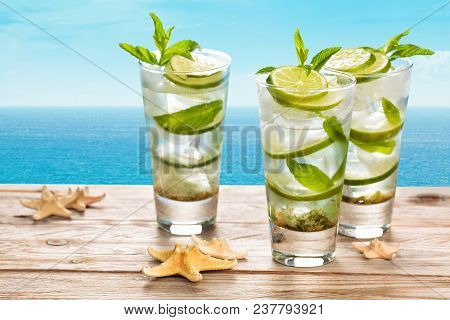 Fresh Mojito Cocktail On Blue Rustic Table With Blue Sea In Background.