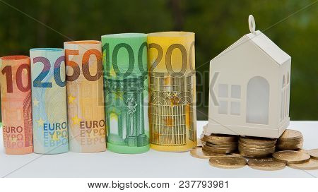 View Of Coin Stack With House Model On Green Background, Savings Plans For Housing, Financial Concep