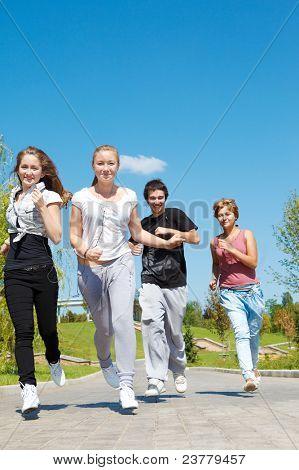 Four happy teen friends running