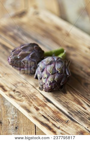 A Pair Of Purple Artichokes Over A Rustic Wooden Table.